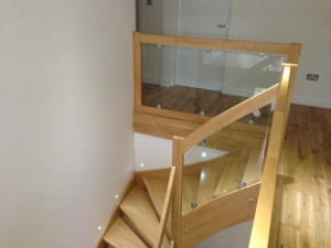 glass balustrades fitted with d-clamps into timber star case