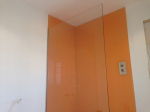 glass shower screen with orange glass splash backs